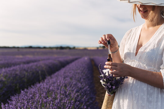 Unrecognizable woman in white dress holding a bottle of lavender oil.