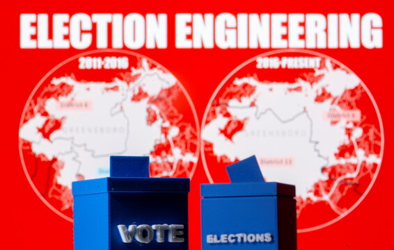 A 3D printed ballot boxes are seen in front of displayed North Carolina district maps in this illustration