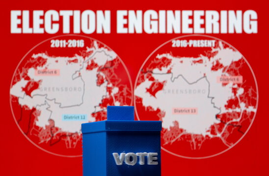 A 3D printed ballot box is seen in front of displayed North Carolina district maps in this illustration