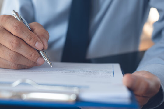 Businessman working in office and signing business document, close up