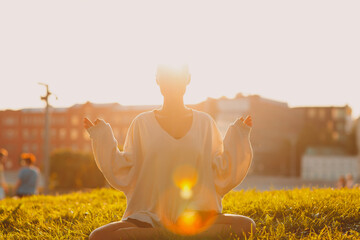 Portrait of young millenial european short haired woman doing yoga lotus asana on green grass meadow summer park sunset. Beautiful happy blonde girl outdoor.
