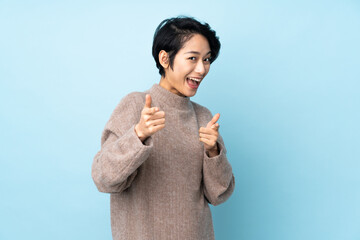 Fototapeta Young Vietnamese woman with short hair over isolated background surprised and pointing front obraz