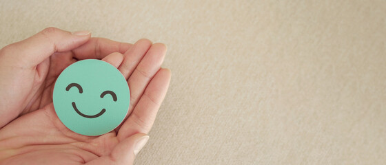 Hands holding green happy smile face paper cut, good feedback rating and positive customer review,...