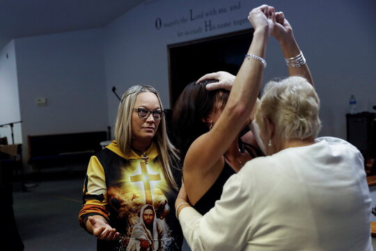 Congregants speak in tongues and pray for a woman, amid the coronavirus disease (COVID-19) pandemic, at the non-denominational Bergman Upper Room Church in Harrison, Arkansas