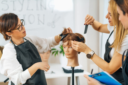Hairdressers Training with Mannequin Head in Education Center