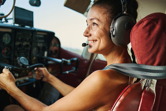 Positive delighted female person flying the plane