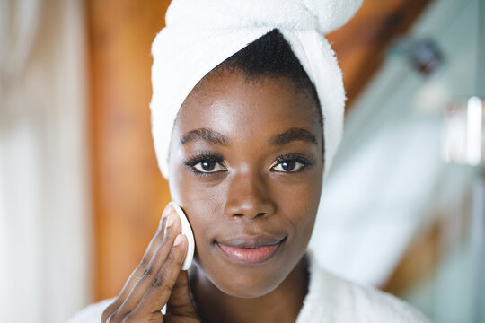 Portrait of smiling african american woman in bathroom, cleansing face with cotton pad for skin care