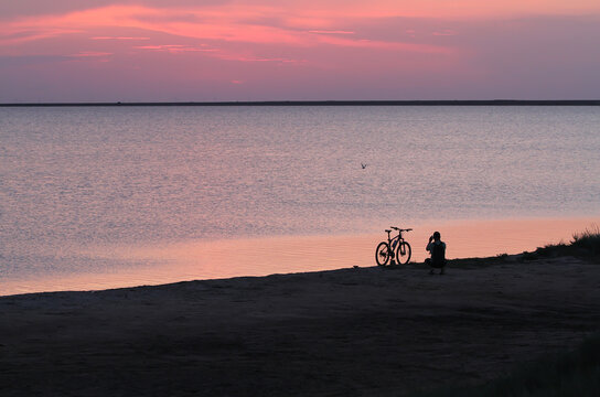 The man next to the bike is filming the sunset near the water