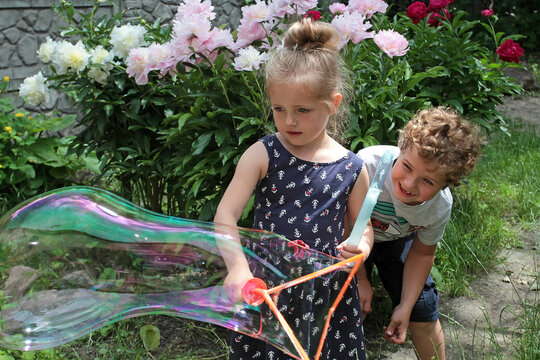 Girl and boy play soap bubbles on a background of flowers