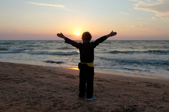 A boy stands with his arms outstretched meets the dawn by the ocean
