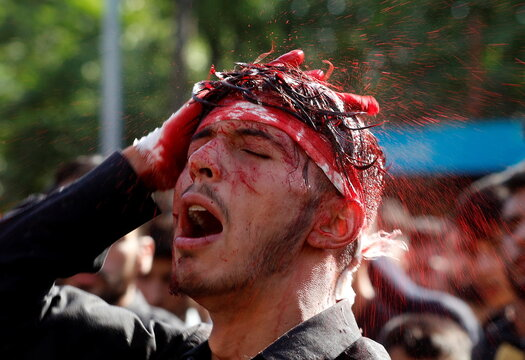 A Kashmiri Shi'ite Muslim mourner reacts as he bleeds after he flagellated himself during a Muharram procession ahead of Ashura in Srinagar