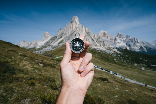 Hand holding compass against Passo Giau mountains in background in Dolomites alps, Italy. Travel adventure concept