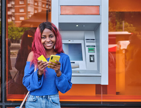 Woman with smartphone and credit card near ATM machine