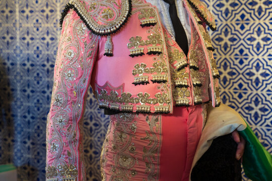 Crop bullfighter in pink and golden traditional costume