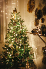 Stylish Christmas tree decorated with modern white baubles, boho ornaments and golden lights on background of paper stars on wall and stocking. Atmospheric festive scandinavian room. Magic time