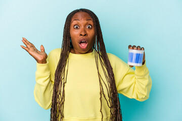 Obraz Young african american woman holding cotton bulls isolated on buds background surprised and shocked. - fototapety do salonu
