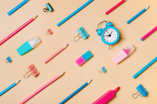 Creative student desk modern school supplies on neutral pastel beige background. Top view flat lay. Back to school concept. Diagonal pattern with pencils, pens, markers, alarm clock, stationery clips