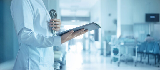 Fototapeta Healthcare and medical concept. Medicine doctor with tablet and stethoscope in hand and patient waiting for examinationon in hospital background. obraz
