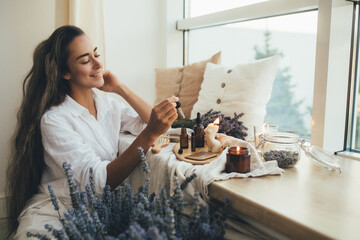 Fototapeta Young woman applying natural organic essential oil on hair and skin. Home spa and beauty rituals. obraz