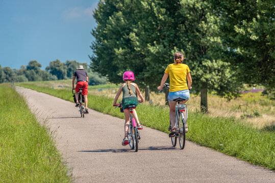 A father, mother and daughter are cycling on a Dutch dike. The little girl is wearing a pink bicycle helmet. It is a sunny day in summertime. The photo was taken in the province of North Brabant.