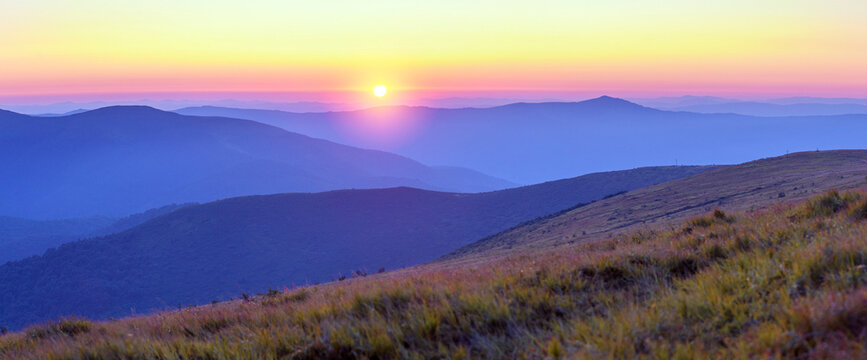 Mountain landscape at sunrise in Eastern Carpathians. Amazing view on colorful clouds and layered mountains. Panoramic view