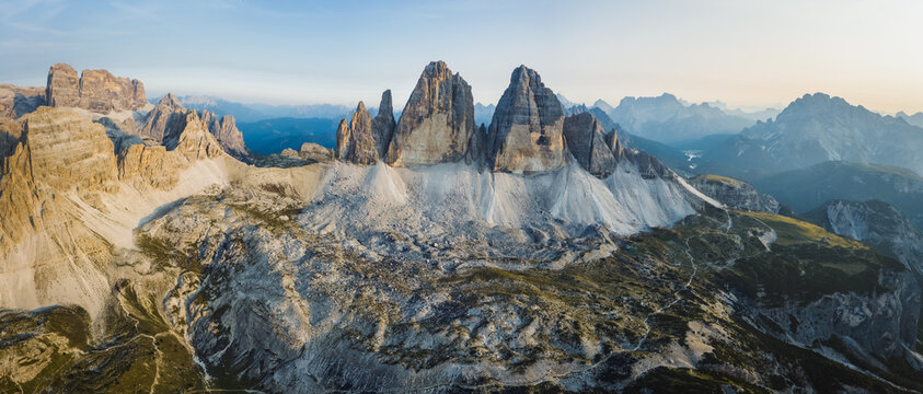 Aerial stitched panoramic photo of Tre Cime di Lavaredo lit by sunset evening light. Dolomites, Italy