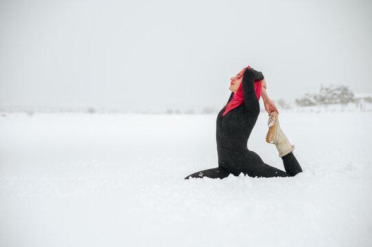 Flexible woman doing yoga in Mermaid pose in winter