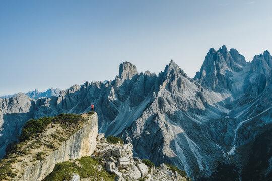 Aerial view of a man on cliff edge admiring epic Cadini di Misurina mountain peaks, Italian Alps, Dolomites, Italy, Europe.