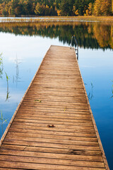 Wooden jetty by a lake with autumn colors in the forest