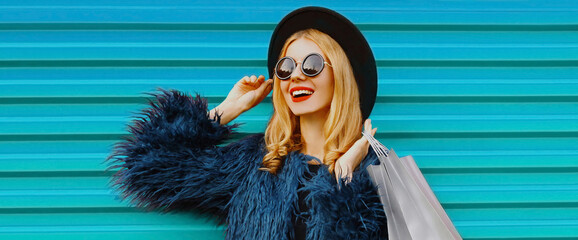 Fashionable portrait of stylish blonde woman with two shopping bags wearing a blue faux fur coat, black round hat on colorful background