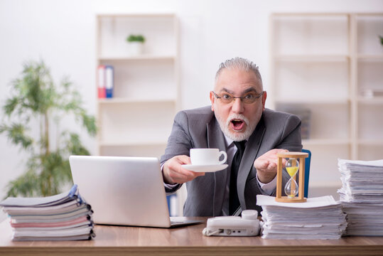 Old male employee drinking coffee during break