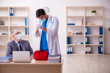 Obraz Young male doctor visiting old businessman at workplace - fototapety do salonu