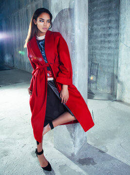 young pretty african american woman in luxury red coat posing fashionable on empty parking building, lifestyle rich people concept