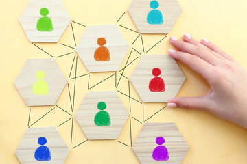 image of tangram blocks with people icons over wooden table ,human resources and management concept