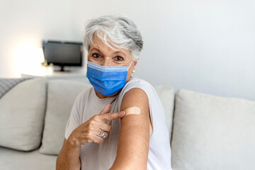 Obraz Mature woman against white background after receiving COVID-19 vaccination, wearing protective face mask. Old Caucasian lady holding up shirt sleeve to show the sticking plaster after a flu jab in arm - fototapety do salonu