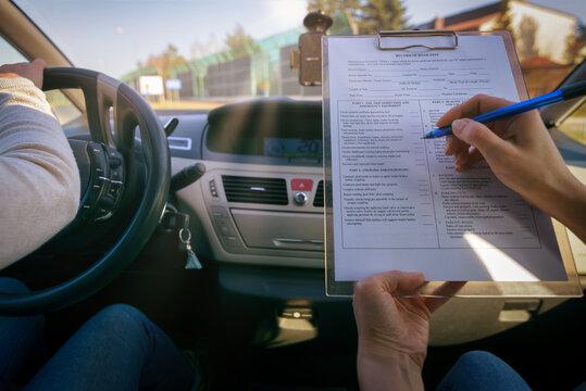 Examiner filling in driver's license road test form