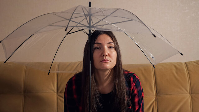 Upset brunette lady hides from water flowing from upstairs neighbors under transparent umbrella sitting on sofa in dark room close-up. Concept of flooding the apartment and property insurance
