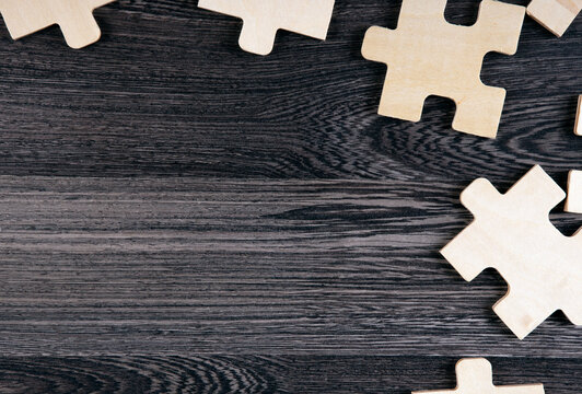 puzzle elements on a wooden background as a riddle