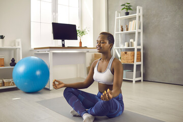 Happy calm beautiful short haired black woman in modern activewear doing yoga on floor at home, enjoying meditation in cross legged lotus pose with eyes closed, relaxing and restoring positive energy