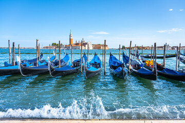 Moored gondolas at St. Mark Square with Church of San Giorgio Maggiore on background. Venice, Italy