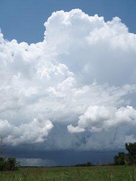 Towering cumulus clouds over Kansas field.