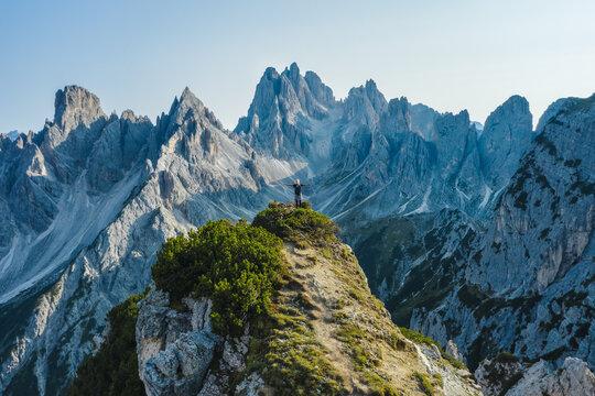 Aerial view of a woman hiker raising her hands on mountain top enjoying Cadini di Misurina mountain peaks, Italian Alps, Dolomites, Italy, Europe