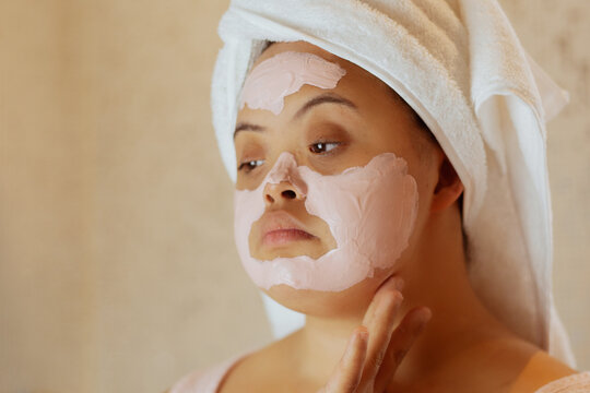 Young biracial woman with Down Syndrome applying face mask in the bathroom