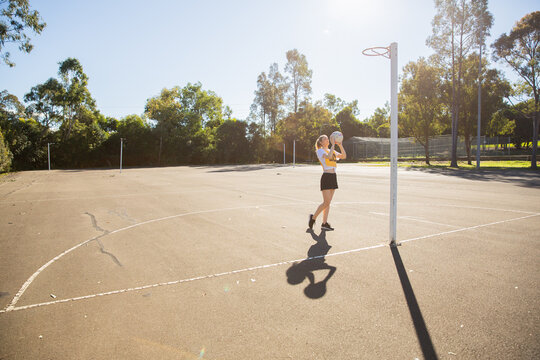 horizontal shot of young woman in sporty clothes holding a net ball in the air with one foot raised