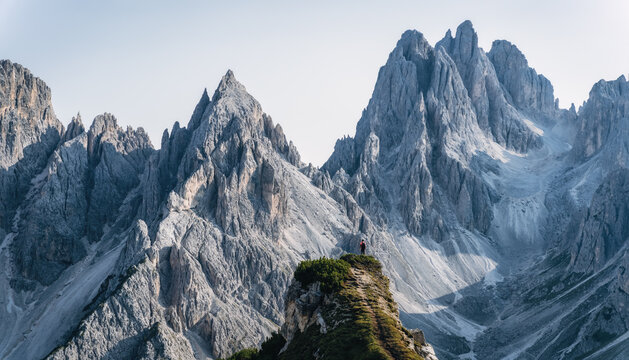 Man hiker standing and admiring stunning beauty of impressive jagged peaks of Cadini di misurina mountain group in Dolomites, Italy, part of Tre Cime di Levaredo national park