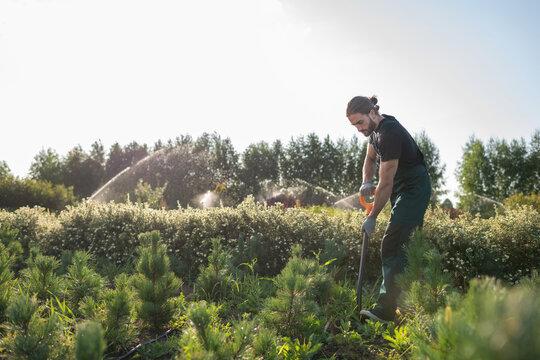 Male farmer digging soil in garden