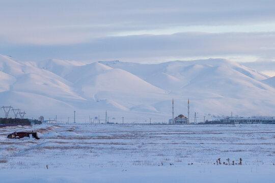 Mosque on distance on snow with Palandoken mountains in Erzurum, Turkey