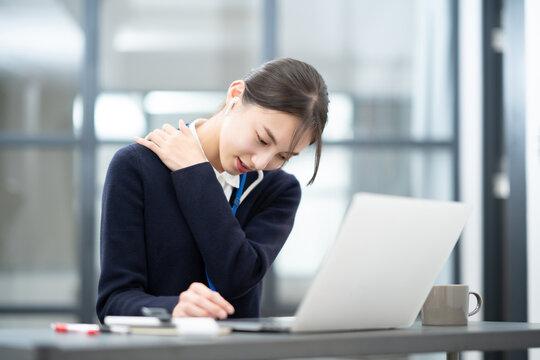 デスクワークで肩こりに悩む若い女性