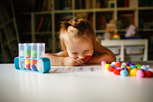 Cute Caucasian child on the table plays with balls and test tubes, the child studies the color using the game. Sensory development and homemade lessons, dark style in the real interior, close up
