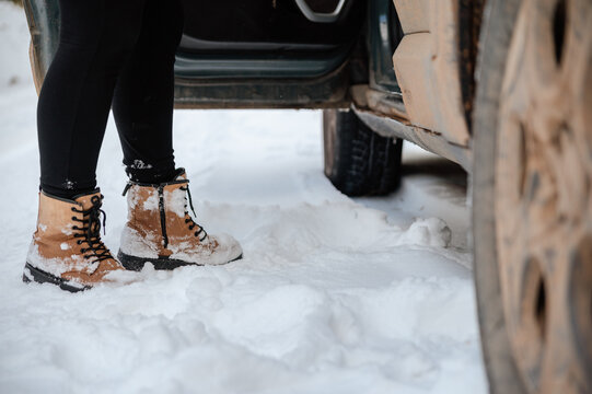 Crop woman getting out of car in winter forest